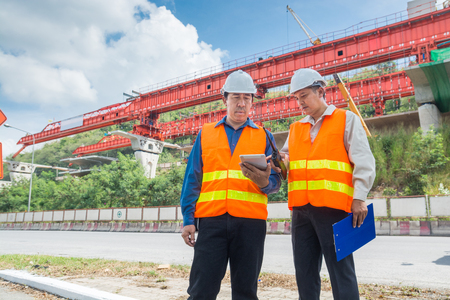 Engineer or Architect consult over Digital Tablet to supervise or manage Motorway or Highway Project Development as Construction industrial concept.