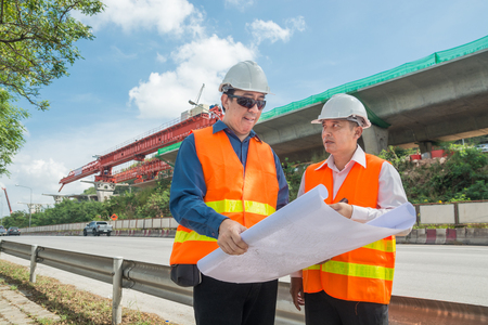 Engineer and Architect or Foreman wear white hardhat and Glow safety cloth meeting in construction site and control Highway Project Development as heavy industrial concept. Standard-Bild