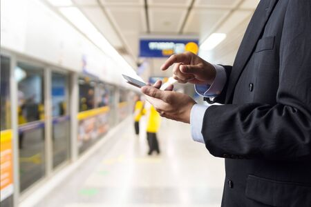 Hand of Businessman hold Wireless Digital Smart Device or Smartphone while waiting for Subway Train in Railway Station Standard-Bild