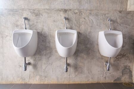 Close up of White Male urinal with Bare cement wall