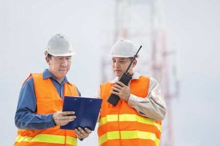 Engineer or Businessman and Architect use portable Radio and Ring binder while discuss on Telecommunication Tower Construction Project as Communication Technology concept. Standard-Bild