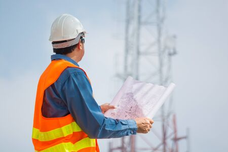 Engineer or Technocian hold plan and look at Telecommunication tower base Station or Network Cell site as Communication Technology Concept.