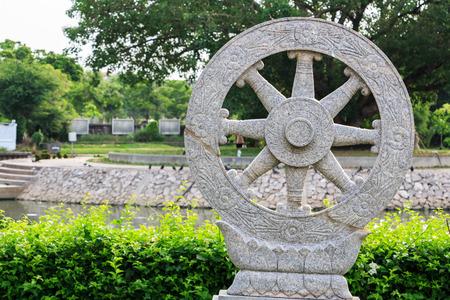 dhamma: wheel of dhamma in garden in temple of thailand.