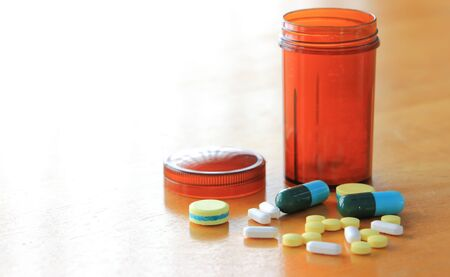 drugs: Many types of medicines on a wood table refers to health care.
