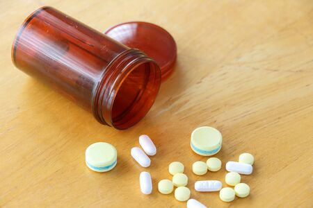 refers: Many types of medicines on a wood table refers to health care.