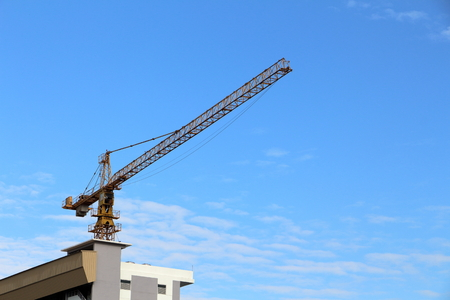Save Download Preview crane Construction on the building blue sky.
