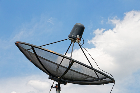 The black satellite dish on the roof on a white cloud background and blue sky, Meaning of Communication and Technology.