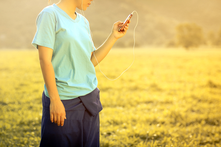 Using Smartphone - Woman holding a smartphone listening to music with retro filter effect Stock Photo