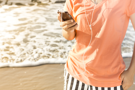 Woman using a smartphone enjoy listening to music lifestyle , Filtered images color effect Stock Photo