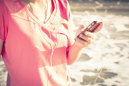 Woman using a smartphone enjoy listening to music lifestyle , Filtered images color effect photo