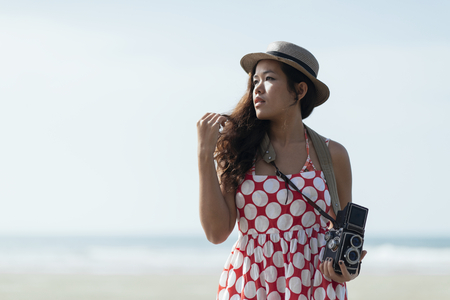 Woman With Vintage Camera On Beach photo