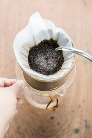 Making brewed coffee from steaming filter drip style. photo