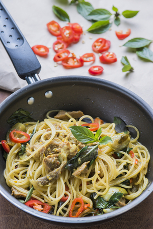 Spaghetti fried with Thai green curry in pan. photo