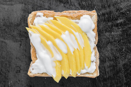 Top view of toast topping with ripe mango and yogurt. Stock Photo