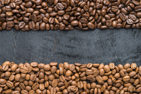 Coffee beans of arabica and robusta  on black wooden background with blank space.