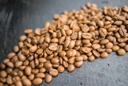 Coffee beans of arabica on black wooden background. Stock Photo