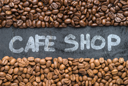 Coffee beans with Cafe Shop hand writing on black wooden background with blank space.