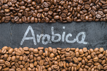 Coffee beans with Arabica hand writing on black wooden background with blank space.