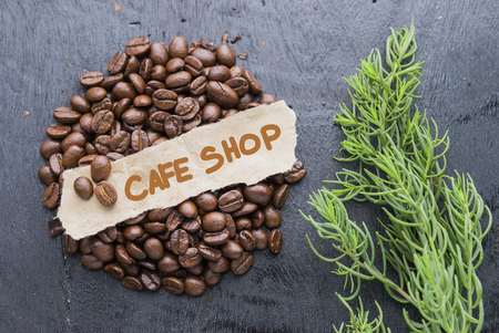 Coffee beans with Cafe Shop label on black wooden background.