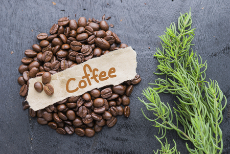 Coffee beans with Coffee text label on black wooden background.