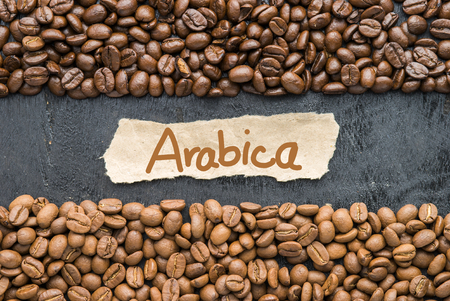 Coffee beans with Arabica label on black wooden background. Stock Photo