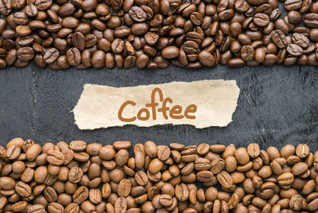 Coffee beans with Coffee label on black wooden background.