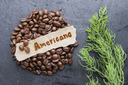 americano: Coffee beans with Americano paper label on black wooden background.