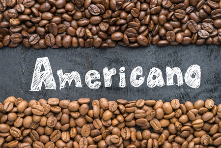 americano: Coffee beans with Americano hand writing on black wooden background with blank space.