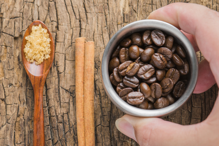 Coffee beans of arabica on texture wooden background.