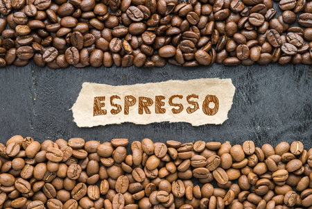 Coffee beans with Espresso paper label on black wooden background. Stock Photo