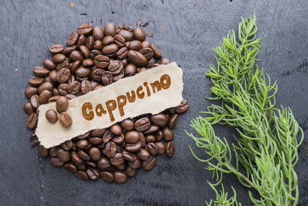 cappucino: Coffee beans with Cappucino paper label on black wooden background. Stock Photo
