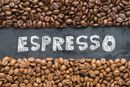 Coffee beans with Espresso hand writing on black wooden background with blank space.