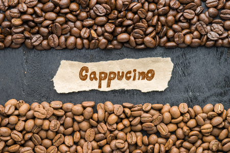 Coffee beans with Cappucino paper label on black wooden background. Stock Photo