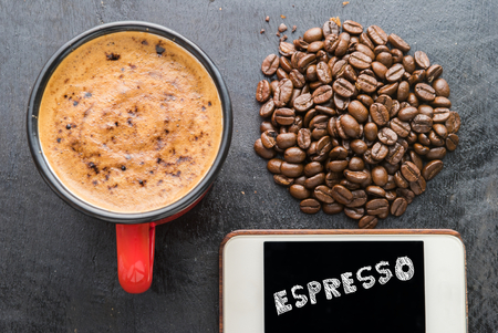 Cup coffee with smartphone Espresso text screen on black wooden background.