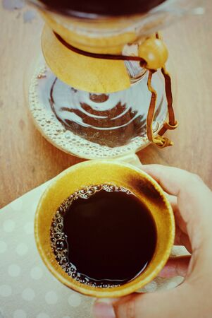 Cup of espresso coffee in homemade cafe shop. Photo in vintage color tone style.