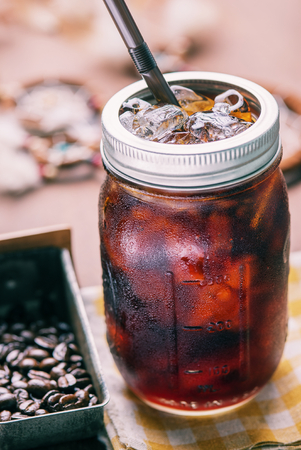 cold meal: Cold arabica coffee with iced in vintage jar. Photo in vintage color tone style.