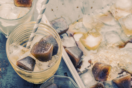 Iced coffee homemade making from ice cubes coffee frozen served in a glass. Photo in vintage color tone style.
