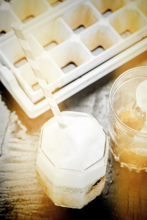 Iced coffee latte homemade making from ice cubes coffee frozen served with milk. Photo in vintage color tone style.
