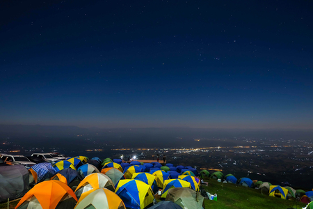 Night mountain landscape with illuminated tent. Silhouettes of snowy mountain peaks and edges night sky with many stars and milky way on background illuminated orange tent on foreground Stock Photo