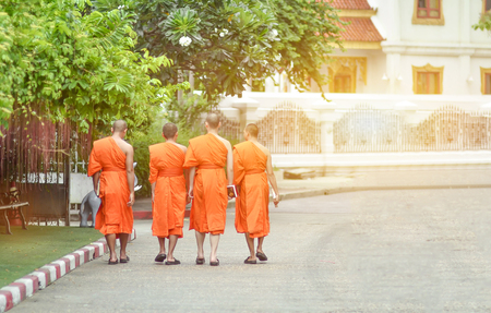 four Monks walking on ancient temple Thailand Stock Photo
