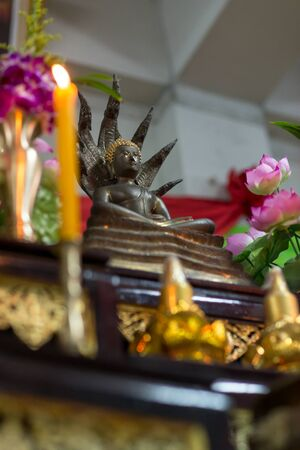 offerings: A statue of Lord Buddha with Nagas on a pedestal with offerings.