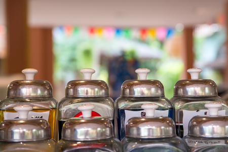 lids: Close-up detail of glass syrup jars with metal lids. Stock Photo