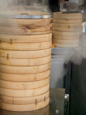 culinary tourism: Chinese dim sum getting steamed in bamboo steamer baskets, at a restaurant.