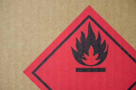 fire hazard: Close-up detail of a fire hazard warning symbol on a cardboard cargo box containing chemicals. Stock Photo