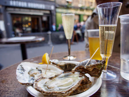 Wide closeup of a plate of raw oysters served with sparkling Prosecco wine outdoors at Borough Market. London, United Kingdom. Travel and seafood cuisine.