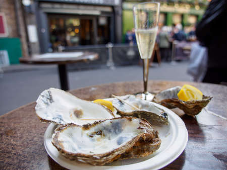 Wide closeup of a plate of eaten empty oyster shells with sparkling Prosecco wine in the background. Borough Market, London, United Kingdom. Travel and seafood cuisine. Banco de Imagens