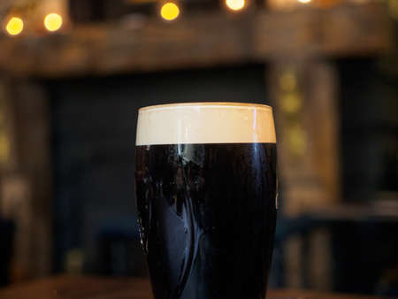 Close-up detail of a glass of cold stout lager in a traditional British pub. Windsor, United Kingdom. Drinks and cuisine.