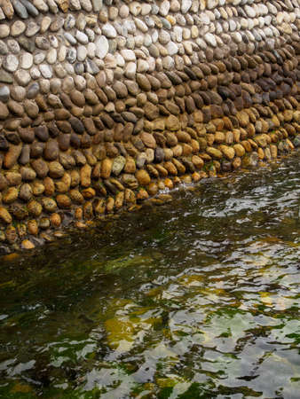 Closeup of a stone wall on the edge of an industrial pier, wet with water and algae. Miyajima Island, Hiroshima, Japan. Vertical orientation. Travel and nature.