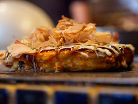Closeup macro detail of a freshly cooked Okonomiyaki with Katsuobushi, dried fish flakes, sauce, and mayonnaise, on a Teppan grill. Shallow focus. Dotonbori, Osaka, Japan. Travel and cuisine. Stock Photo