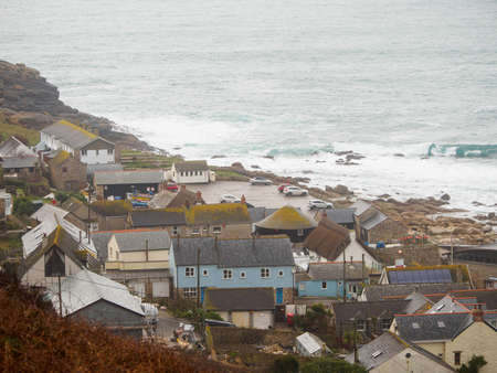 Wide aerial view of the buildings and rocky coasts of the fishing village of Sennen Cove on a stormy day. Sennen, England. Travel and Cornish tourism.